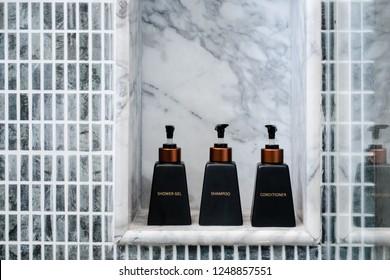 Bathroom toiletries on marble shelf. Grey blue mosaic tile. Minimalism concept