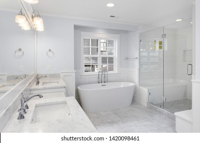 Bathroom with two sinks, bathtub, and shower in new luxury home