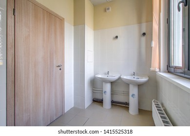 Bathroom with two sinks. Public restroom in kindergarten, pool or school. Toilet with shower cabinet. WC. Moscow 2019