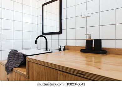Bathroom vanity of wood with black basin and taps