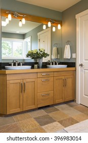 Bathroom vanity with wood cabinets, double sinks, slate tile floors and accent lighting in contemporary upscale home interior