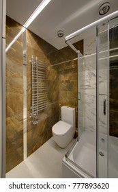 A bathroom with a wall from brown marble and a shower cabin