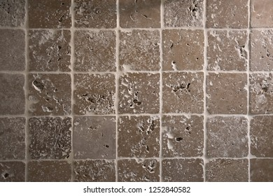 Bathroom wall covered with rough square tiles. Interior tiles. Grunge background. Surface of wall tile facing. Porous textured tiles backdrop.