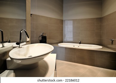 A bathroom with wash basin in the foreground and bath in the background.