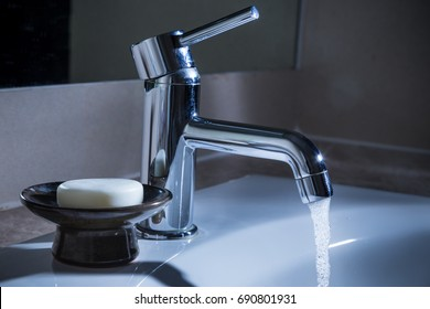 Bathroom Water Faucet With Water Running At Night, Concept For Waste  Resource