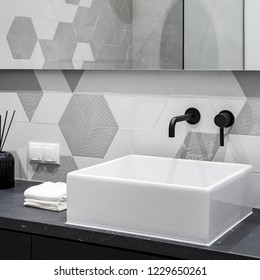 Bathroom with white, square countertop washbasin with black faucet