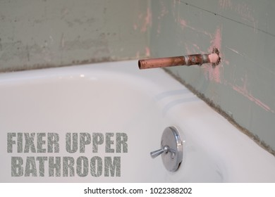 BATHTUB WITH COPPER TUBING FOR DOWNSPOUT READY FOR INSTALLING NEW TILES WITH WORD FIXER UPPER BATHROOM AT THE CORNER / BATHROOM RENOVATION