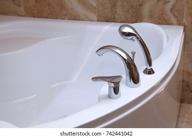 Bathtub faucet in modern bathroom. White bath tub with faucet and beige tiles. Detail of bathroom, selective focus