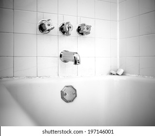 A bathtub and its faucet and three turning knobs.