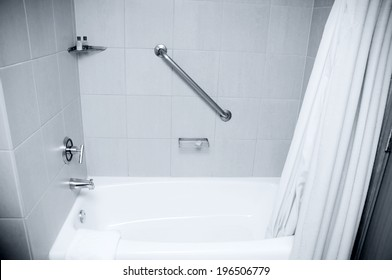 A bathtub with a shower and a handicapped hand rail.