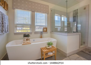 Bathtub and shower stall in front of windows with valance and blinds