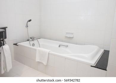 bathtub with shower in white bathroom