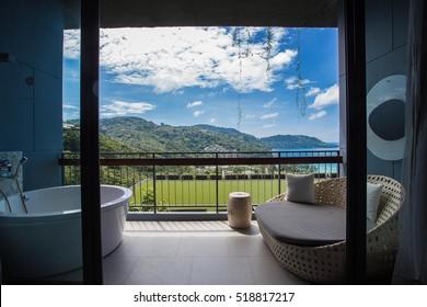Bathtub and sofa outside at the balcony.