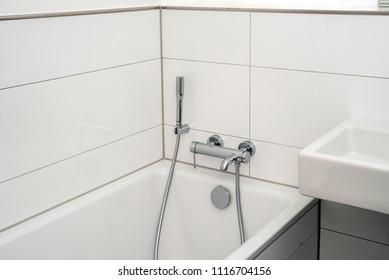 bathub with hose and shower