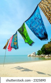 Batik is hanged at the beach. Batik is hand-dyeing clothes, is traditional handicraft in tropical country like Malaysia and Hawaii.