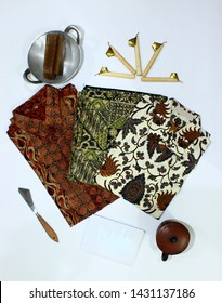 batik, hem with motive batik, clothes with batik motive, canting, cup of pottery, little pan and wax isolated on white background, traditional fashion