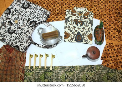 batik, tote bag with batik motive, woman shirt blouse, hem with motive batik, clothes with batik motive canting, duck wood and cup of pottery isolated on white background, traditional fashion