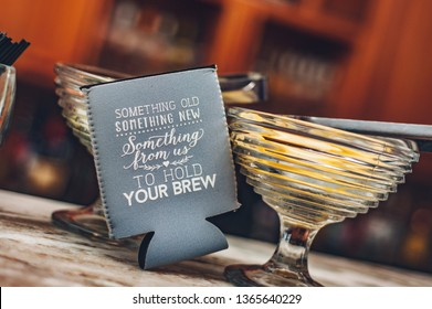 BATON ROUGE, L.A. / USA - APRIL 14, 2018: Beer and beverage coozie. Beer can cooler sleeves for ice cold drinks. Soda or bottle holder novelty huggie. Wedding party favor gifts for the guest to keep.