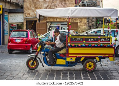 Batroun, Lebanon - October 2018:Lebanese man driving tuk- tuk on the street on coastal Batroun town in Lebanon