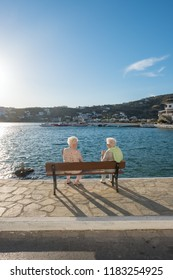Batsi, Greece - May 31, 2018: Unidentified senior ladies talks at seafront bench in picturesque village of Batsi on Andros island, Cyclades, Greece