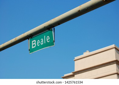 A battered Beale Street sign hanging on a rusty gray pole with a blue sky in the background
