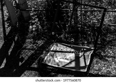A battered and bent pedestrian sign on the ground in monochrome