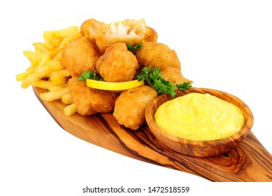 Battered cod nugget bites with potato French Fries and mayonnaise dip on an olive wood serving board isolated on a white background