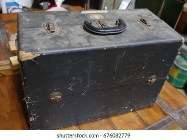 Battered and dusty black wooden chest with rusty knobs and locks