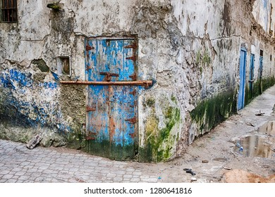 A battered old blue door with a bar for security in a run-down neighborhood is located at a street corner in the Mellah portion of Essaouira in Morocco.