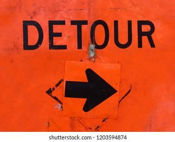 Battered orange DETOUR sign with arrow.