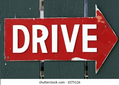 Battered Red Arrow Sign with the Word 'Drive' in White Letters.