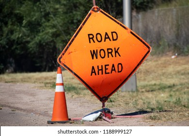 Battered Road Work Ahead sign and traffic cone sitting by road with blurred background