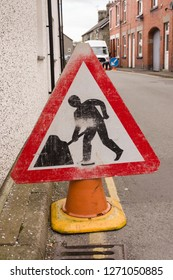 Battered road works sign in an urban terraced street in the United Kingdom