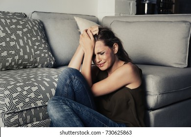 Battered sad woman sitting alone in room