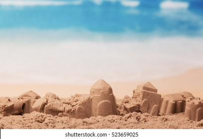 Battered sandcastles on the sunny ocean background