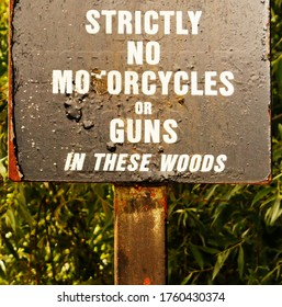 "A battered sign in Bristol, UK says, ""strictly no guns or motorcycles in these woods"". In the background is greenery."