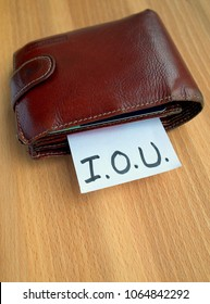 A battered wallet with a note sticking out of it on which someone has written IOU as a concept for money problems and debt