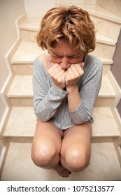 Battered woman sitting on a ladder