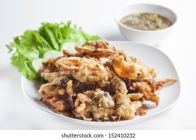 Batter-fried soft shell crab in dish on white background.