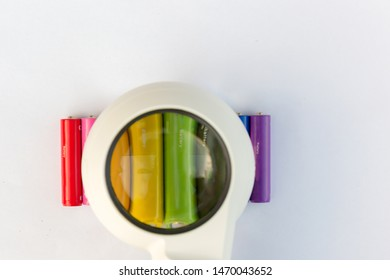 Batteries or accumulators of dimension AA or AAA of all colors of the rainbow lie or stand on a sheet of white paper. Look through the magnifying glass.
