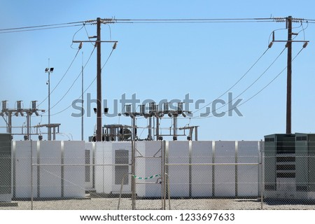 Batteries at Solar Farm on very bright sunny day with Switchgear in background.