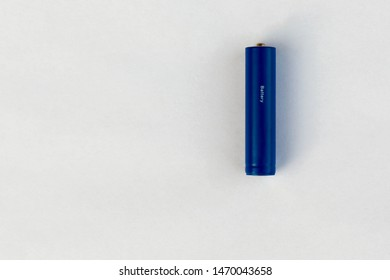 The battery or accumulator of dimension AA or AAA of blue color lies or costs on a sheet of white paper.