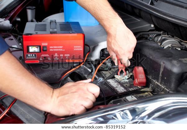 Batterieladegerät und Auto in der Reparaturwerkstatt.