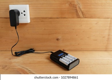 Battery Charger with battery size AA rechargeable with Charger Plug in power outlet adapter on wooden table