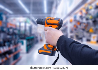 Battery drill or screwdriver in hand, isolated against the background of a hardware store. Construction tool for home and work