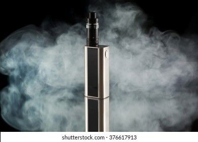Battery mod or e-cigarette with tank at smoke on black background