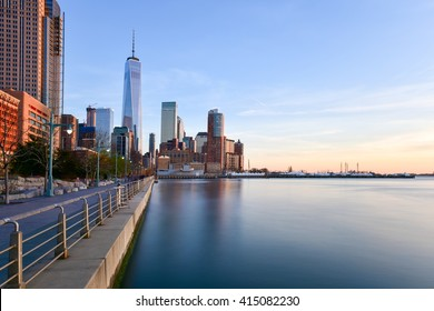 Battery Park and New Jersey skyline at sunset from Manhattan, New York City over the Hudson River.