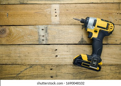 Battery powered impact driver sitting on rough wooden background.