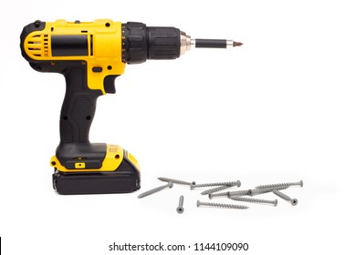 A battery powered screw gun drill next to a pile of screws on a white background text or copy space to the right, home improvement construction DIY remodel power tool concept, horizontal shot, closeup