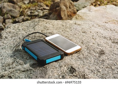 Battery solar energy device on the stone. Charge smart phone from the solar battery.